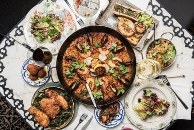 overhead photo of paella dish and side salads