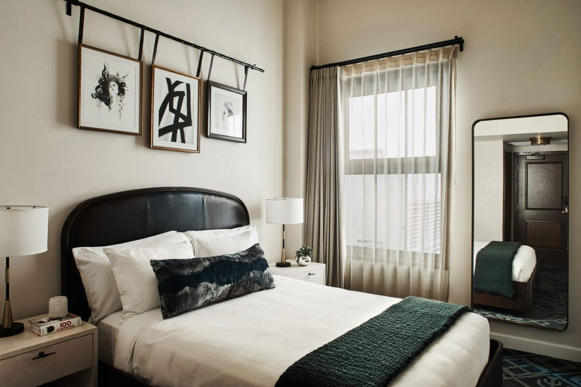 hotel room with bed, nightstands, and large mirror