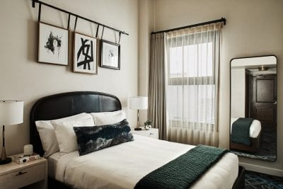 hotel bedroom with nightstands, large mirror and window