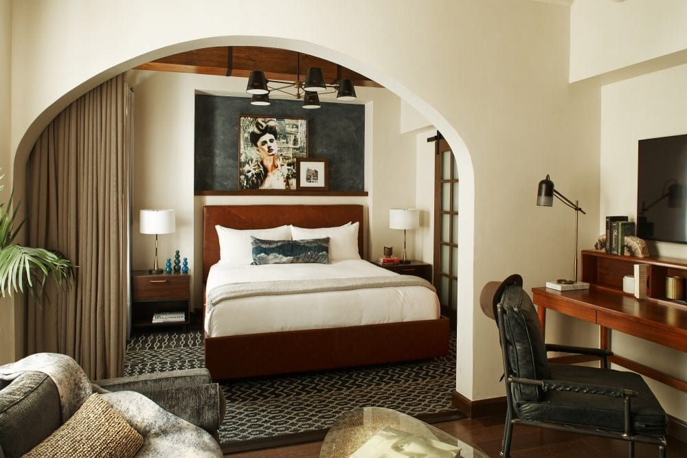 hotel suite with bed and living room with sofa and desk with chair