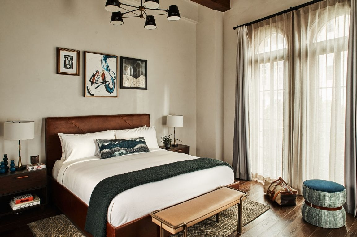 hotel room with bed, nightstands, arched windows and ottoman