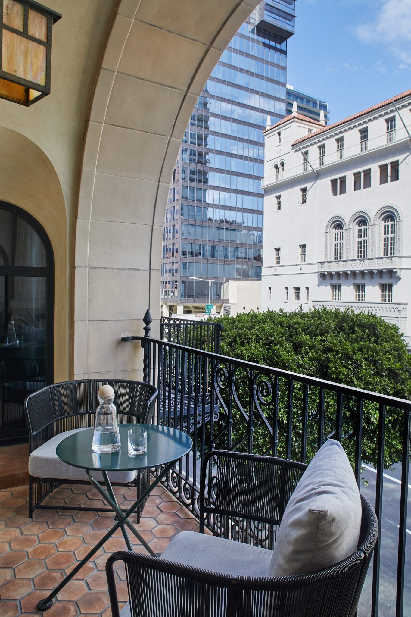 two chairs and a table on a balcony overlooking buildings