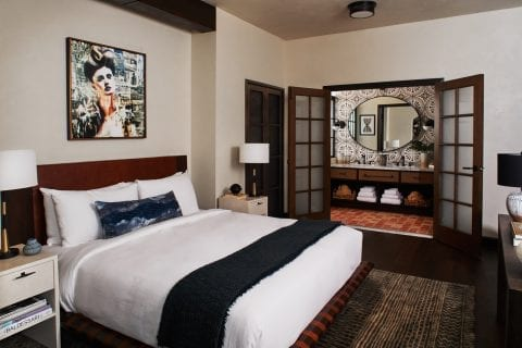 hotel bedroom with nightstands, and bathroom with mirror and towels underneath