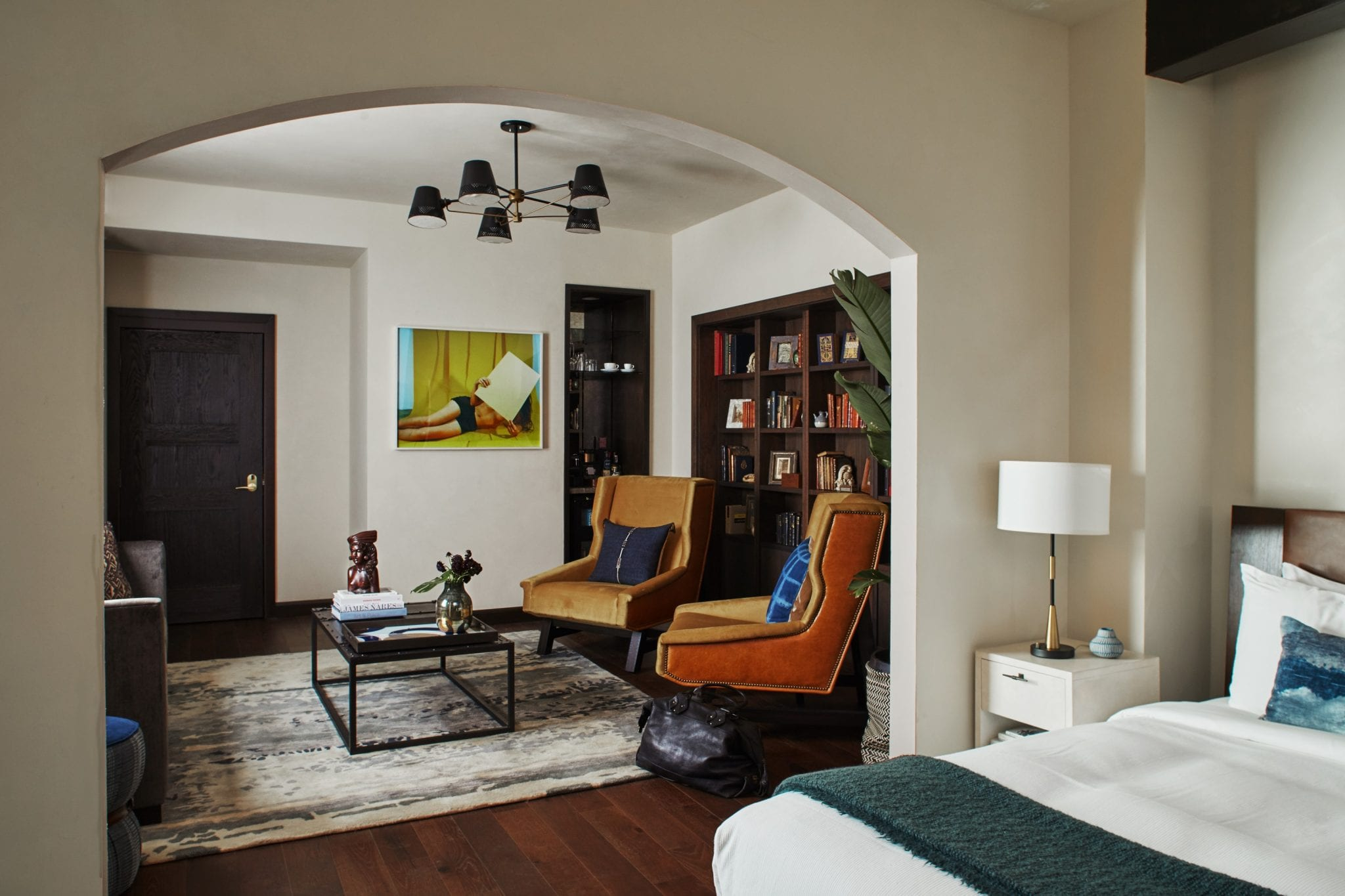hotel suite with view from bedroom to living room with chairs and coffee table