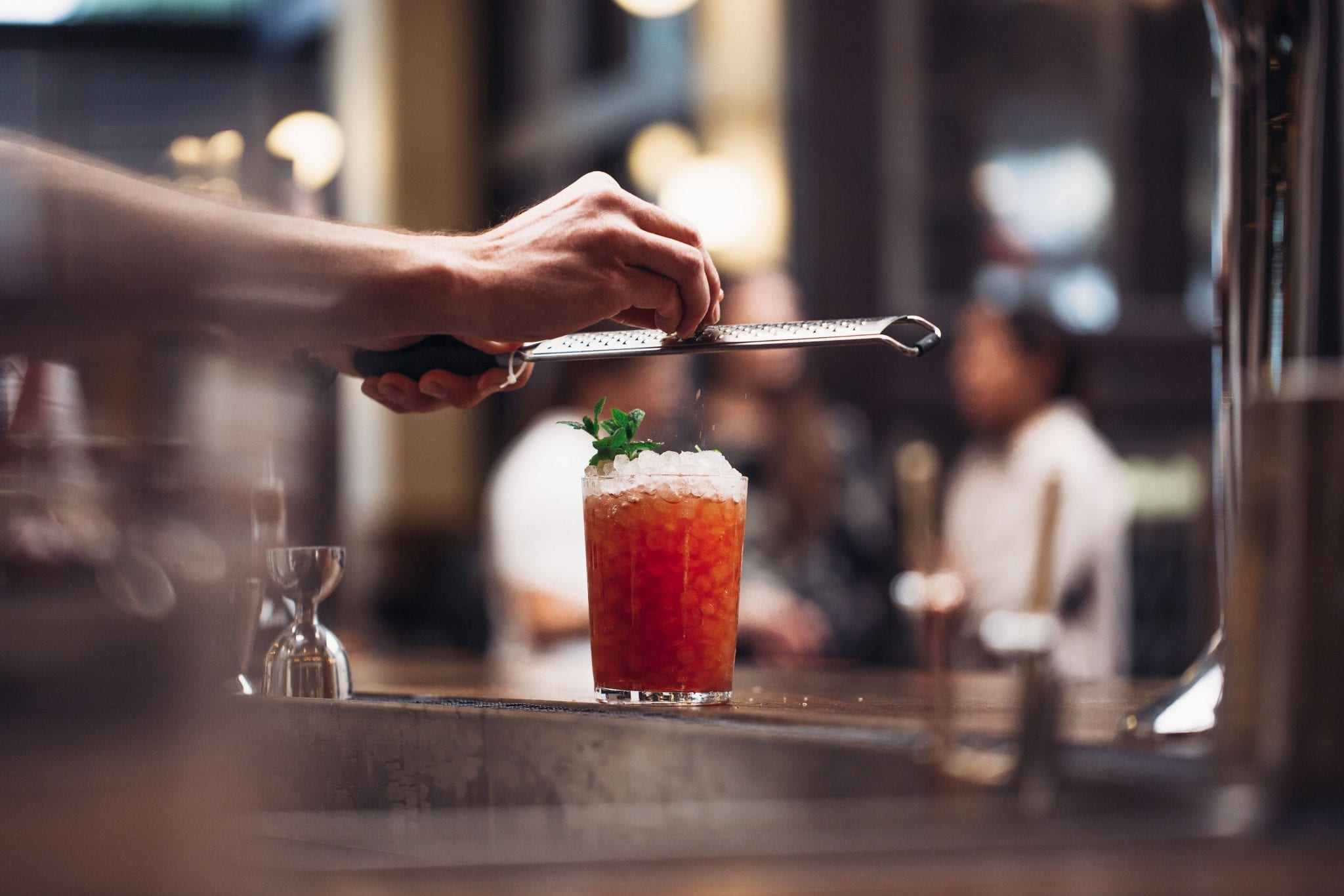 fruit cocktail on table topped with ice while a bartender grates ingredient over glass
