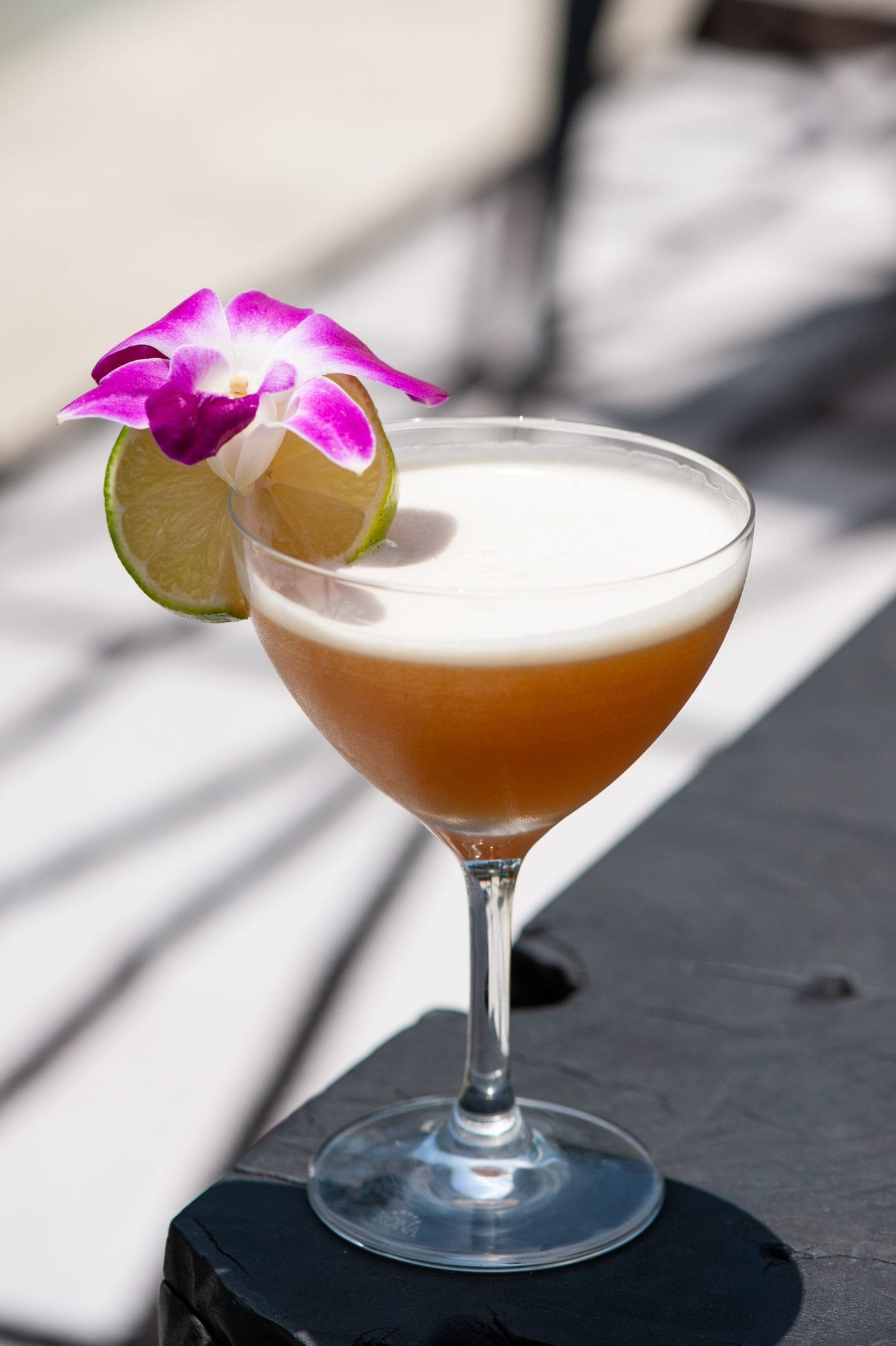 blood and sand cocktail in martini glass with slice of lime and flower