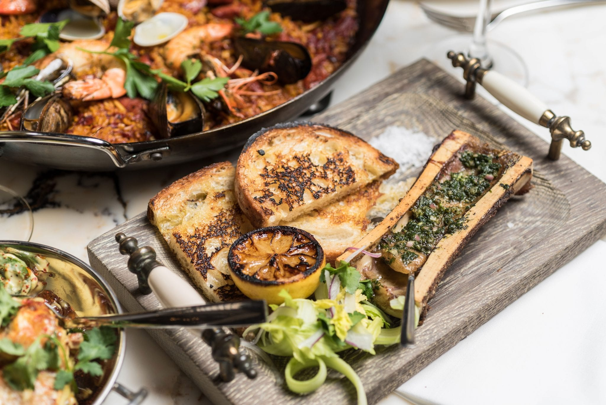 closeup of wooden plate with bone marrow and toasted bread