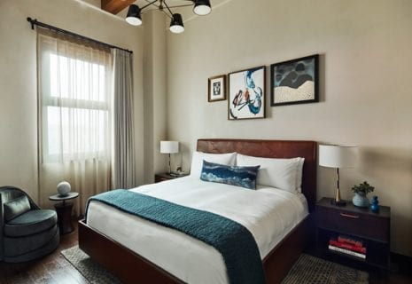 hotel bed with nightstand, lamps, chair, and small table