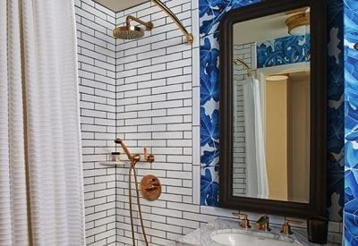 bathroom with sink and mirror next to a shower