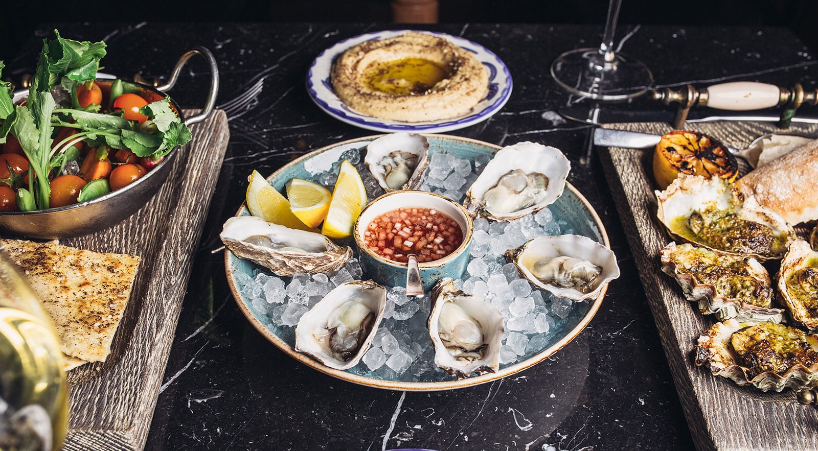 a table with plates of raw oysters, grilled oysters and hummus