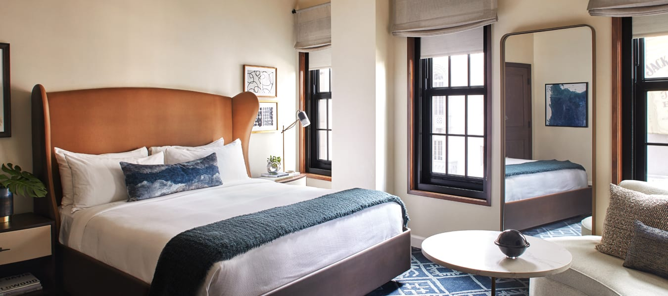 hotel room with bed, nightstands, large mirror, chairs and a small table