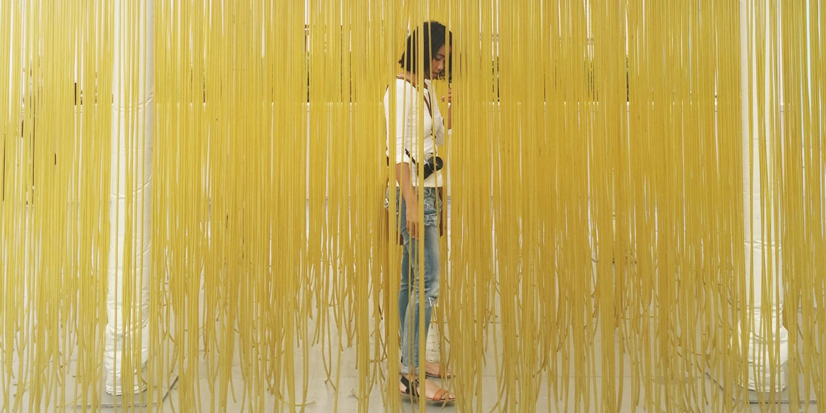 woman standing behind string curtain