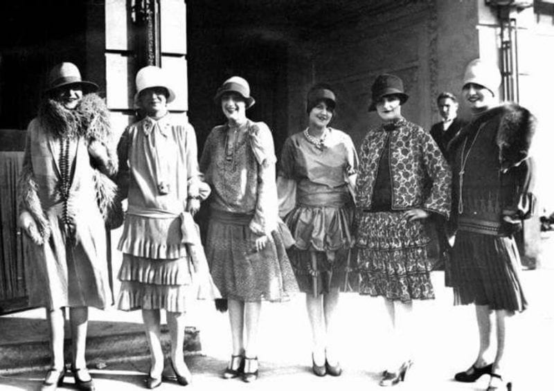 old photo of women dressed in 30s attire, posing for a photo next to each other