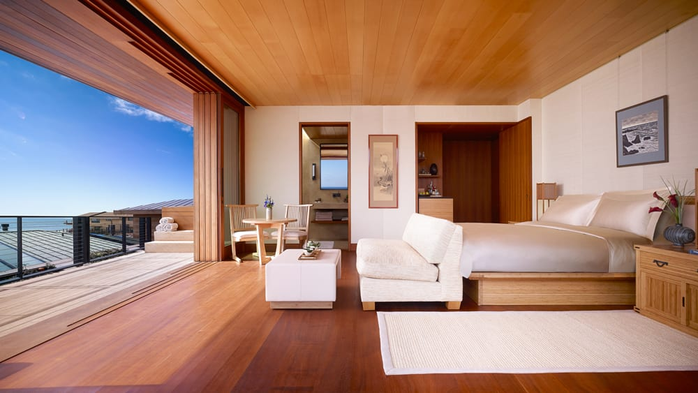 room with bed, sofa, and panoramic view from open wall-to-wall door