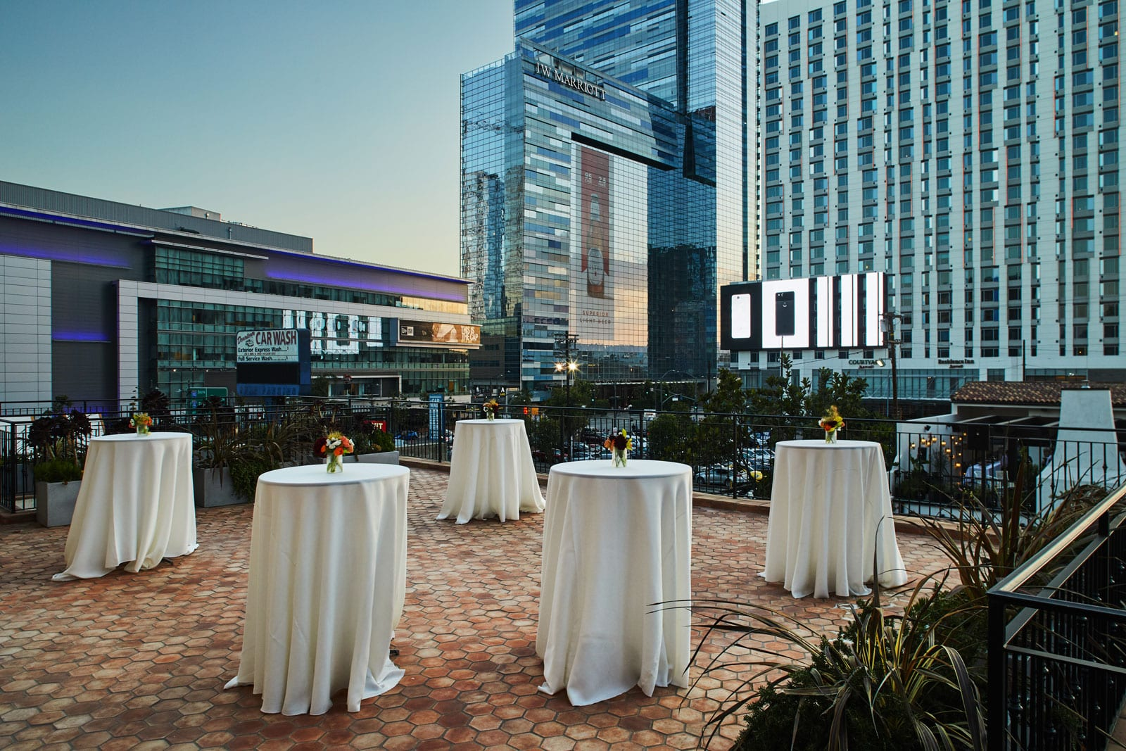 outdoor cocktail tables with buildings in background