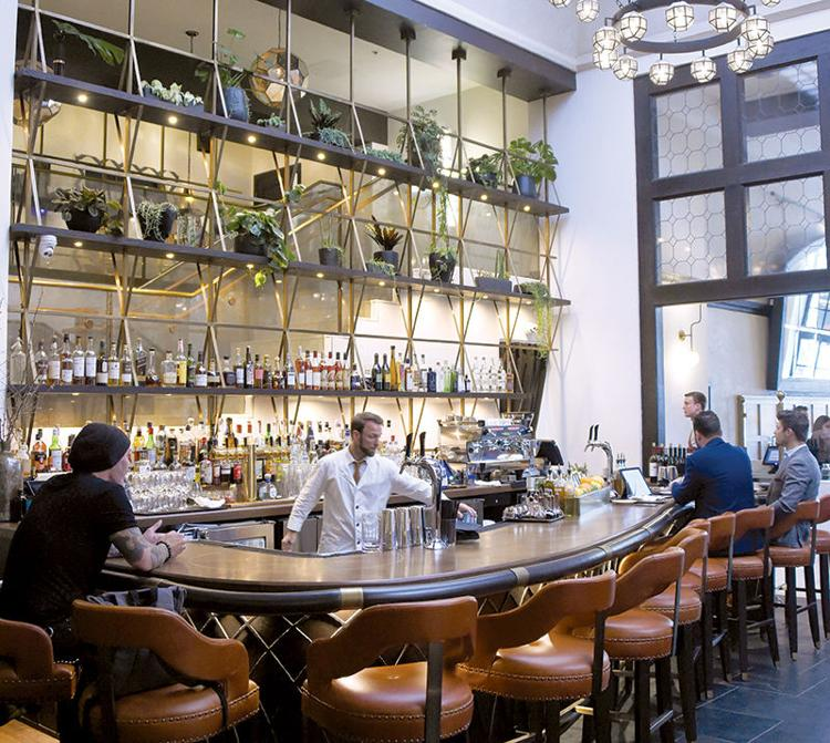 bartender and patrons sitting at curved bar with high ceiling