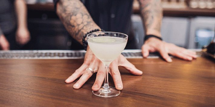 person with arm tattoos touching a cocktail drink on the table