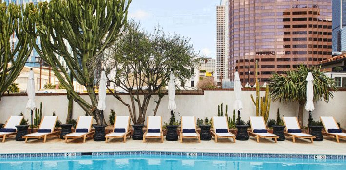 outdoor pool and row of empty lounge chairs