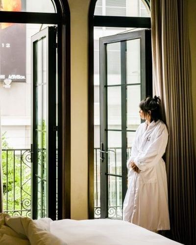 woman wearing bathrobe, looking outside hotel room from balcony door