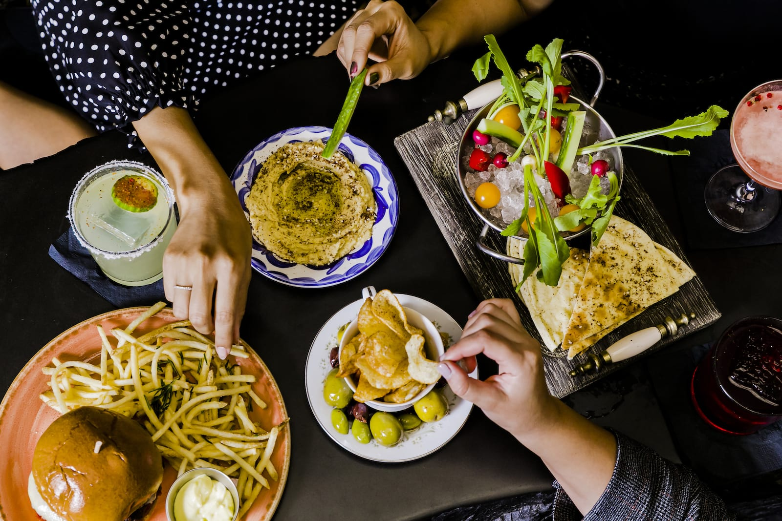 overhead photo of people sharing various dishes