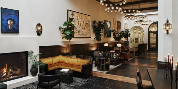 lobby with sofa, fireplace, and tables with chairs
