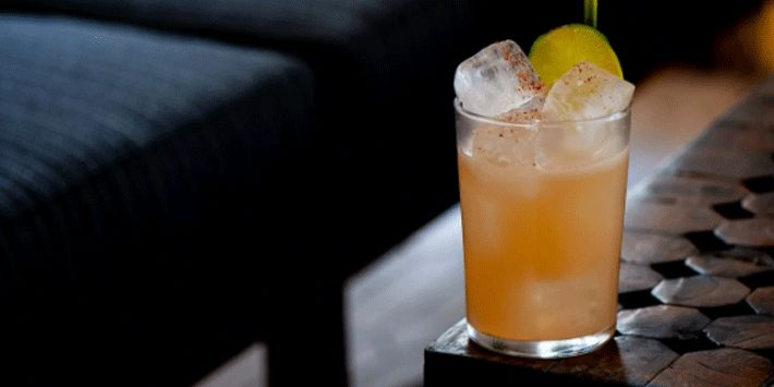 cocktail drink sitting on corner edge of table