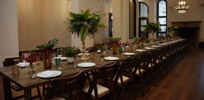 long table with plates, chairs and glasses set up in a hall